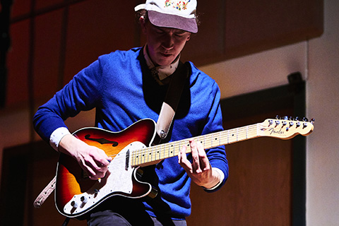 Guitarist with a blue shirt and hat plays on stage